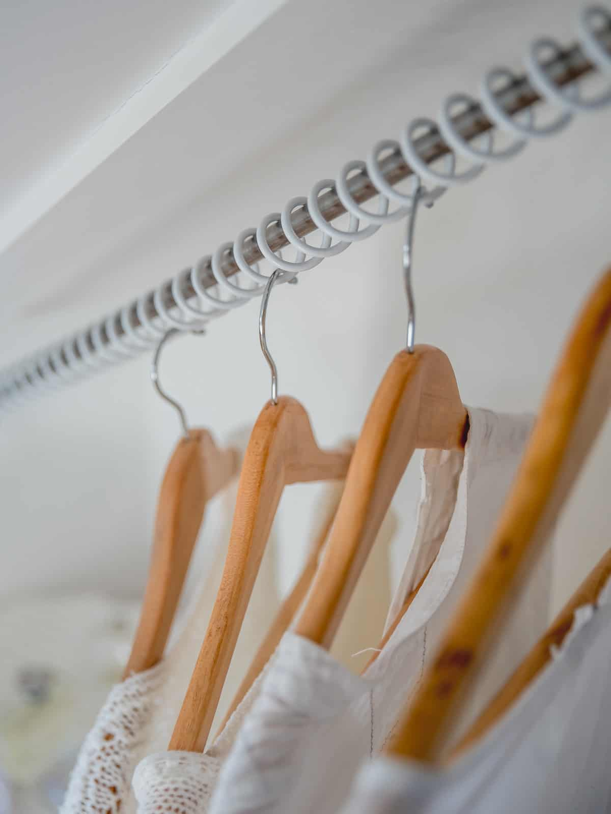 Zebedee Any Angle Hanging Rail - White - shown with clothes hangers